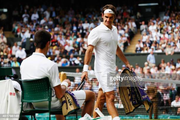 Roger Federer of Switzerland looks over at Novak Djokovic of Serbia as he walks past him during a change of ends during the Gentlemen's Singles Final...