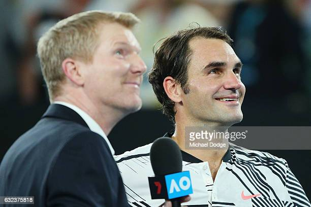 Roger Federer of Switzerland looks up at the video screen with Jim Courier after winning in his fourth round match against Kei Nishikori of Japan on...