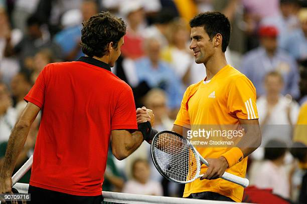 Roger Federer of Switzerland meets Novak Djokovic of Serbia at the net after the Men's Singles Semifinal match on day fourteen of the 2009 US Open at...