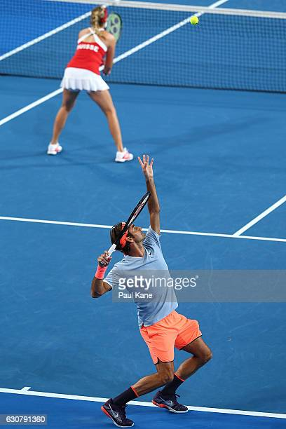Roger Federer of Switzerland partnered with Belinda Bencic serves in the mixed doubles match against Heather Watson and Dan Evans of Great Britain on...