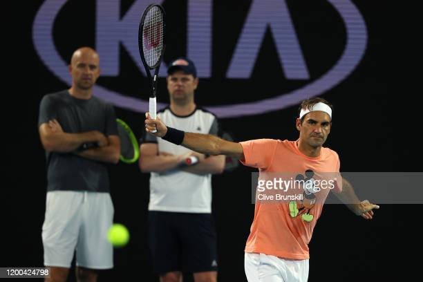 Roger Federer of Switzerland plays a backhand as his coaches Ivan Ljubicic and Severin Luthi look on during practice ahead of the 2020 Australian...