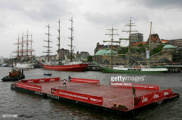 Roger Federer of Switzerland plays against Tommy Haas of Germany on a pontoon being pulled by a tugboat on the River Elbe in the Hamburg Harbour...