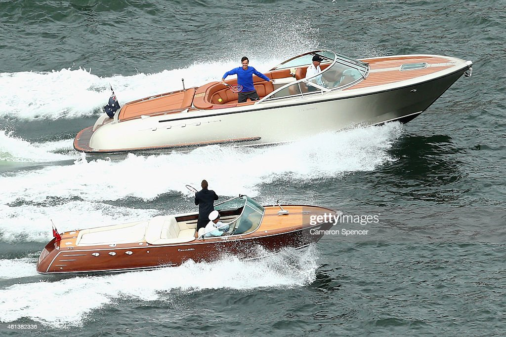 Roger Federer of Switzerland plays tennis with Lleyton Hewitt of Australia between speedboats on Sydney Harbour ahead of their Fast 4 Exhibition match on January 12, 2015 in Sydney, Australia.