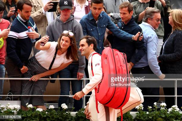 Roger Federer of Switzerland poses for a selfie with a fan following victory during his mens singles first round match against Lorenzo Sonego of...