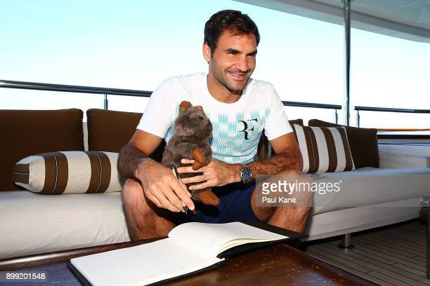 Roger Federer of Switzerland poses for photos with a toy Quokka while signing a guest register on board Anya at Rottnest Island ahead of the 2018...
