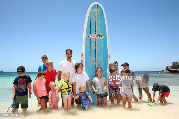 Roger Federer of Switzerland poses with a stand up paddle board and children at Rottnest Island ahead of the 2018 Hopman Cup on December 28 2017 in...