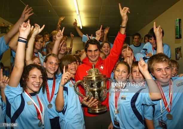 Roger Federer of Switzerland poses with ball kids after winning the Singles Final against Jarkko Nieminen of Finland during Day Six of the ATP...