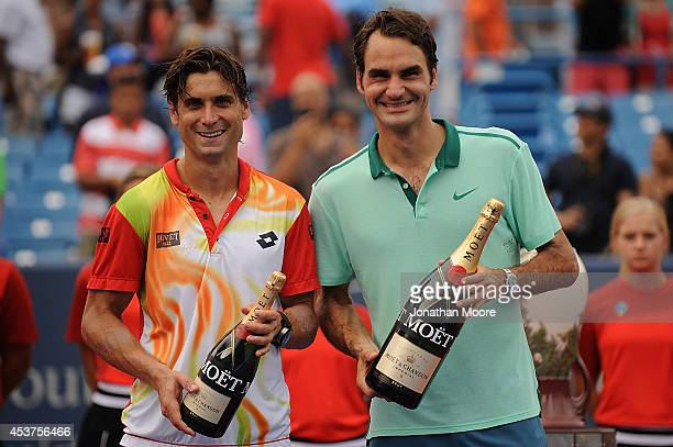 Roger Federer of Switzerland poses with David Ferrer of Spain holding bottles of Moët & Chandon Champagne after winning a final match on day 9 of the...