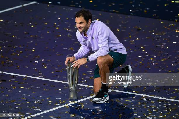 TOPSHOT Roger Federer of Switzerland poses with his trophy after beating Rafael Nadal of Spain in the men's singles final match at the Shanghai...