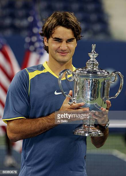 Roger Federer of Switzerland poses with the championship trophy after defeating Andre Agassi in the men's final of the US Open at the USTA National...