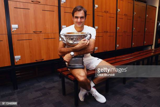 Roger Federer of Switzerland poses with the Norman Brookes Challenge Cup in the players locker room after winning the Men's Singles Final against...