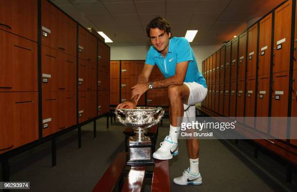 Roger Federer of Switzerland poses with the Norman Brookes Challenge Cup in the players locker room after winning the men's final match against Andy...