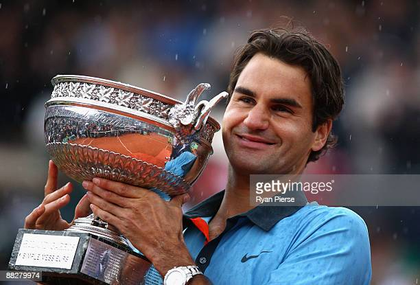 Roger Federer of Switzerland poses with the trophy as he celebrates victory during the Men's Singles Final match against Robin Soderling of Sweden on...