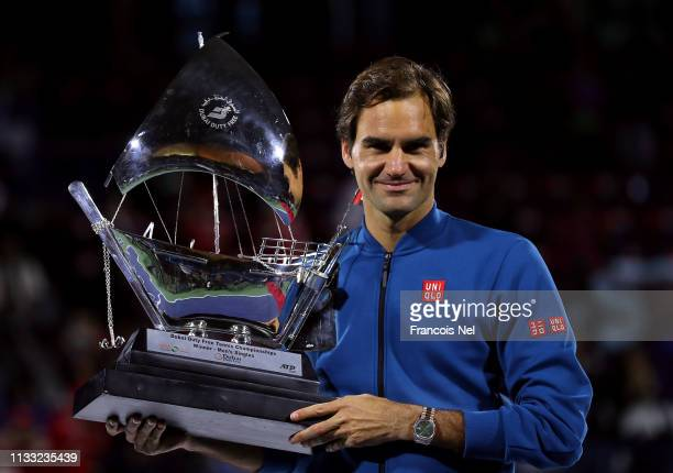 Roger Federer of Switzerland poses with the winners trophy after victory during day fourteen of the Dubai Duty Free Championships at Dubai Tennis...