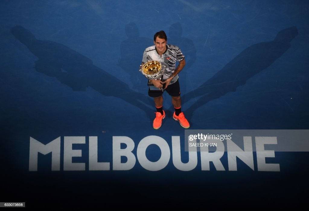 Roger Federer of Switzerland poses with the winner's trophy following his victory over Rafael Nadal of Spain in the men's singles final on day 14 of the Australian Open tennis tournament in Melbourne on January 29, 2017. / AFP / SAEED