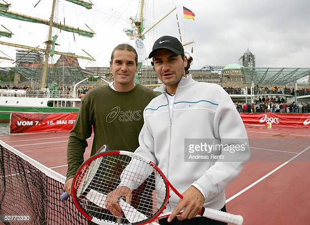 Roger Federer of Switzerland poses with Tommy Haas of Germany on a pontoon being pulled by a tugboat on the River Elbe in the Hamburg Harbour prior...
