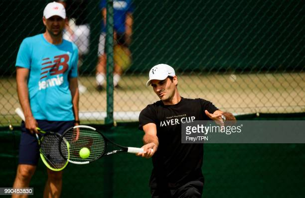 Roger Federer of Switzerland practices with coach Ivan Ljubicic before the start of the Championships at the All England Tennis and Croquet Club in...