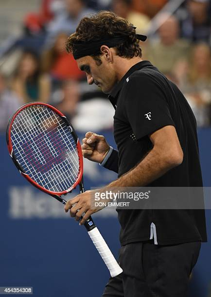 Roger Federer of Switzerland pumps his fist after winning the second set against Sam Groth of Australia during their US Open 2014 men's singles match...