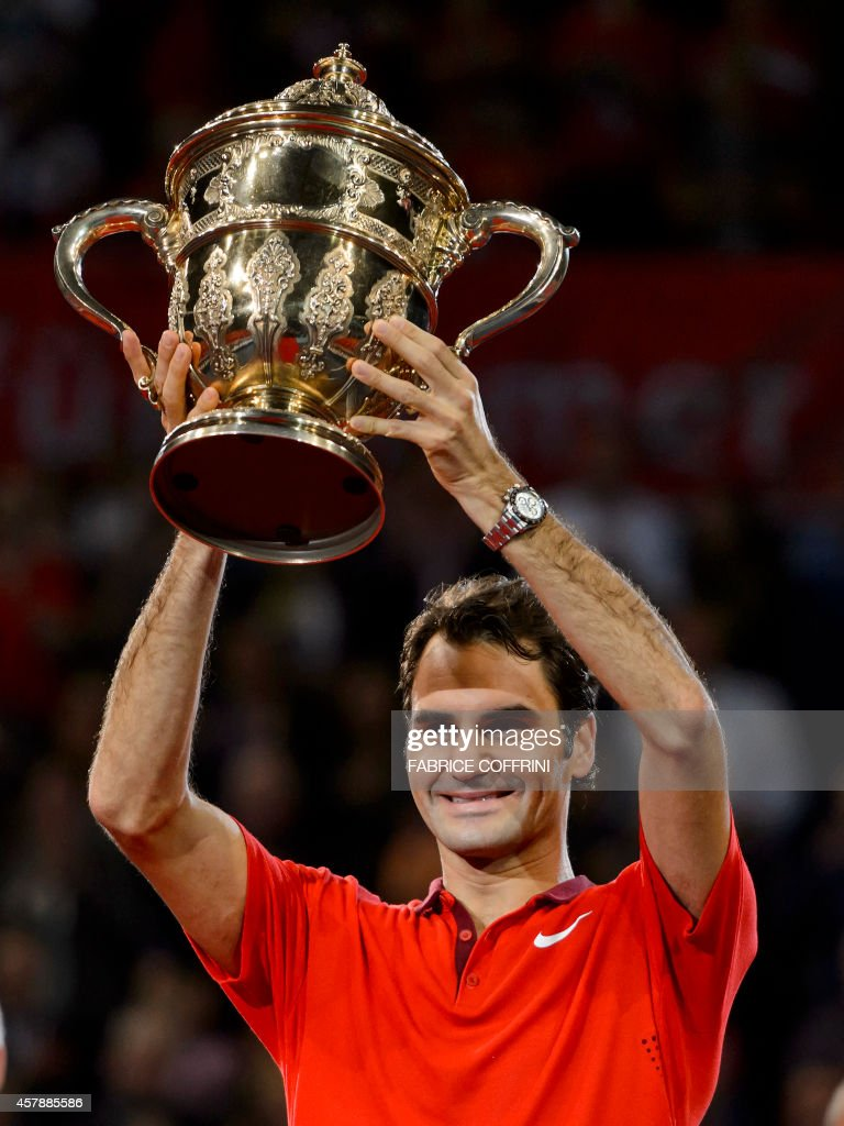Roger Federer of Switzerland raises the trophy after he won his final match against David Goffin of Belgium at the Swiss Indoors ATP tennis tournament on October 26, 2014 in Basel.