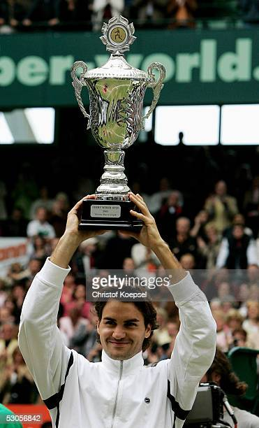 Roger Federer of Switzerland raises the trophy as he celebrates his victory against Marat Safin of Russia in the final of the Gerry Weber Open June...