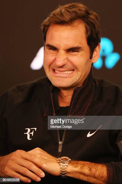 Roger Federer of Switzerland reacts after a journalist hits his head on a broadcast televison camera fixed from the ceiling during a practice session...