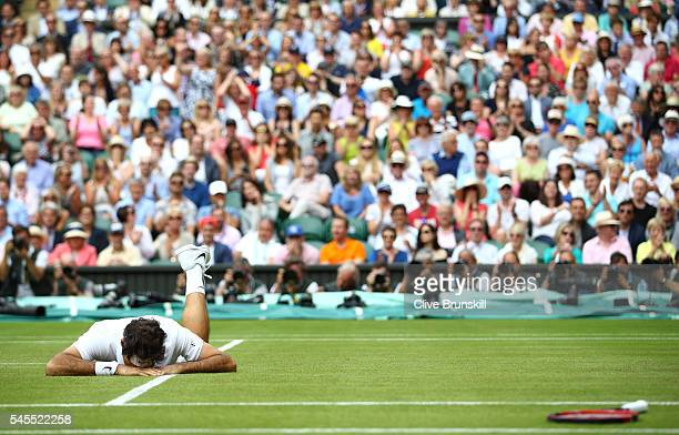 Roger Federer of Switzerland reacts after he slips during the Men's Singles Semi Final match against Milos Raonic of Canada on day eleven of the...