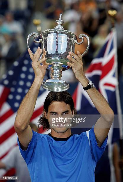 Roger Federer of Switzerland receives the trophy after defeating Lleyton Hewitt of Australia in the men's final match of the US Open on September 12...