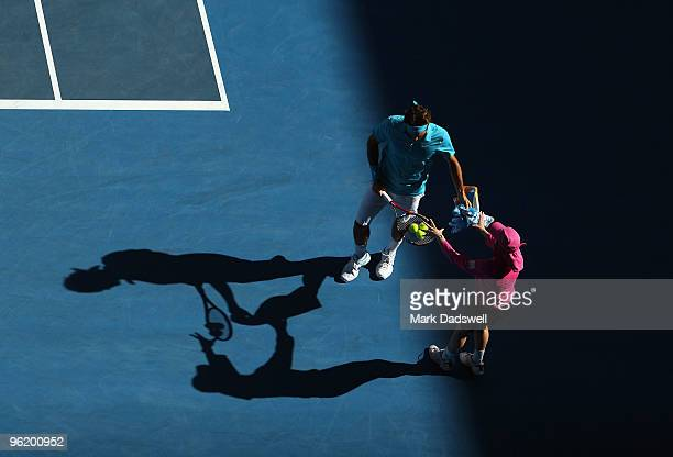 Roger Federer of Switzerland recieves tennis balls from a ball kid in his quarterfinal match against Nikolay Davydenko of Russia during day ten of...