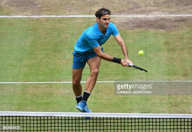 TOPSHOT Roger Federer of Switzerland returns a ball to Borna Coric from Croatia during their final match at the ATP tennis tournament in Halle...