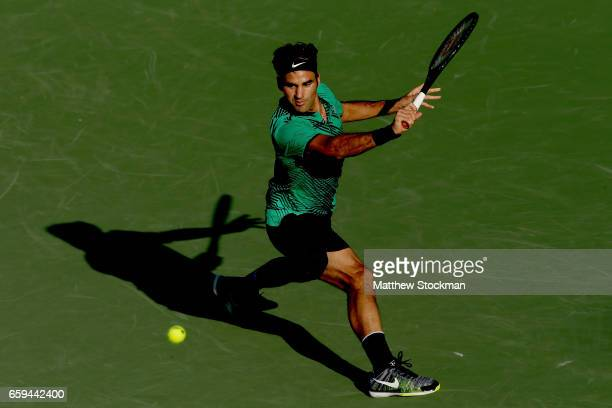 Roger Federer of Switzerland returns a shot to Roberto Bautista Agut of Spain during the Miami Open at the Crandon Park Tennis Center on March 28...