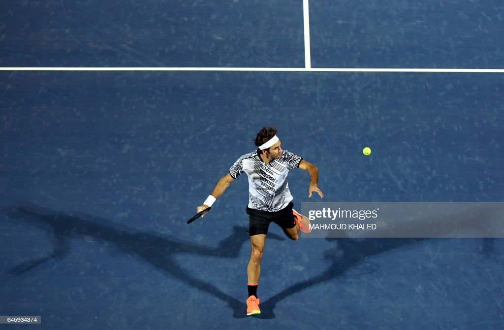 TOPSHOT - Roger Federer of Switzerland returns the ball to France's Benoit Paire during their ATP tennis match as part of the Dubai Duty Free Championships on February 27, 2017. KHALED