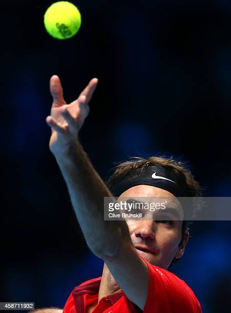 Roger Federer of Switzerland serves against Milos Raonic of Canada during their round robin match during the Barclays ATP World Tour Finals at the O2...