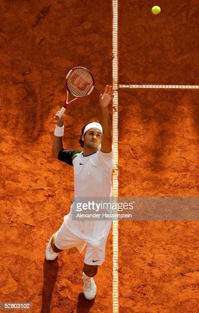 Roger Federer of Switzerland serves during his doubles match with Yves Allegro of Switzerland against Leander Paes of India and Nenad Zimonjic of...