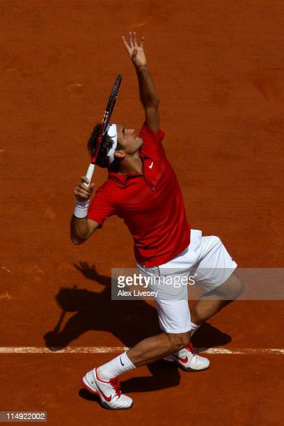 Roger Federer of Switzerland serves during the men's singles round four match between Stanislas Wawrinka of Switzerland and Roger Federer of...