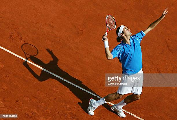 Roger Federer of Switzerland serves in his first round match against Kristof Vliegen of Belgium during Day Two of the 2004 French Open Tennis...