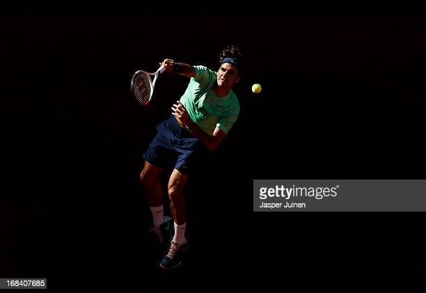 Roger Federer of Switzerland serves the ball during his match against Kei Nishikori of Japan on day six of the Mutua Madrid Open tennis tournament at...
