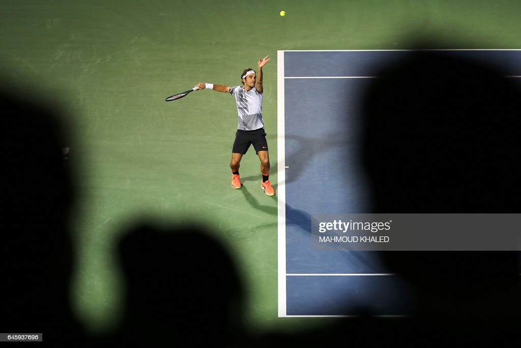 TOPSHOT - Roger Federer of Switzerland serves the ball to France's Benoit Paire during their ATP tennis match as part of the Dubai Duty Free Championships on February 27, 2017. KHALED