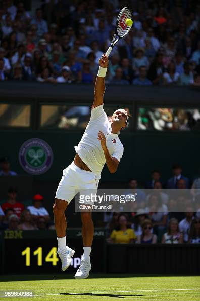 Roger Federer of Switzerland serves to Dusan Lajovic of Serbia during their Men's Singles first round match on day one of the Wimbledon Lawn Tennis...