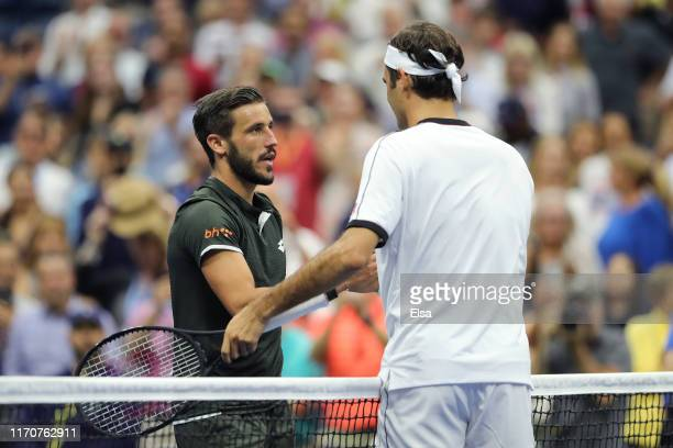 Roger Federer of Switzerland shakes hands with Damir Dzumhur of Bosnia and Herzegovina following their Men's Singles second round match on day three...