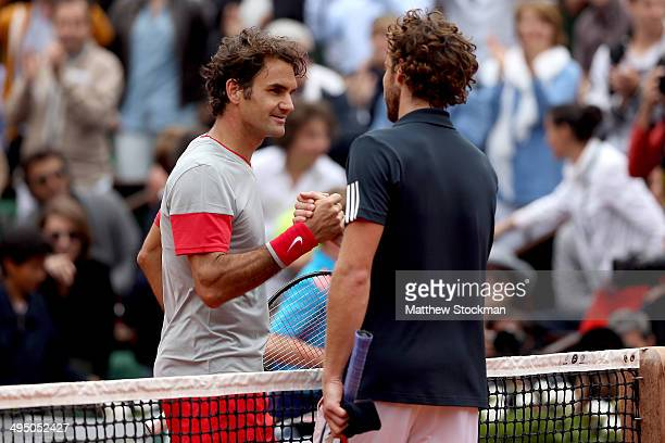 Roger Federer of Switzerland shakes hands with Ernests Gulbis of Latvia at the net following his defeat in their men's singles match on day eight of...