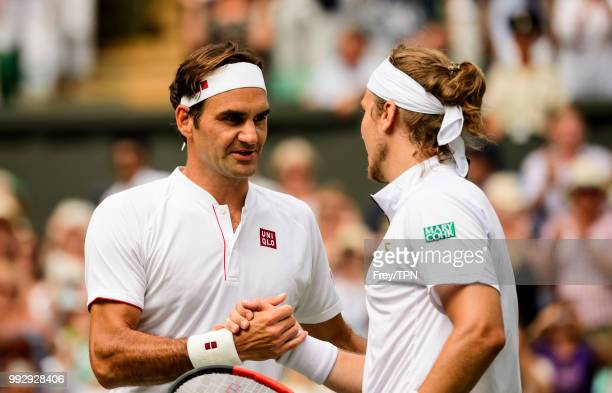 Roger Federer of Switzerland shakes hands with Lukas Lacko of Slovakia after winning their second round match at the All England Lawn Tennis and...