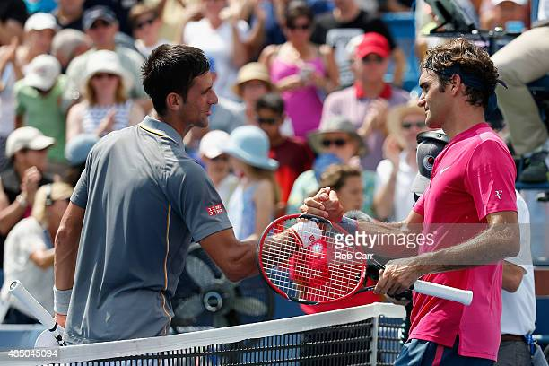 Roger Federer of Switzerland shakes hands with Novak Djokovic of Serbia after defeating him in two sets to win the mens singles final at the Western...
