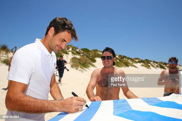 Roger Federer of Switzerland signs a beach umbrella for a beach goer at Rottnest Island ahead of the 2018 Hopman Cup on December 28 2017 in Perth...