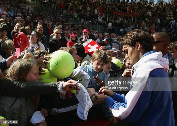 Roger Federer of Switzerland signs autographs for fans after his victory against Juan Carlos Ferrero of Spain during day four of the Tennis Masters...