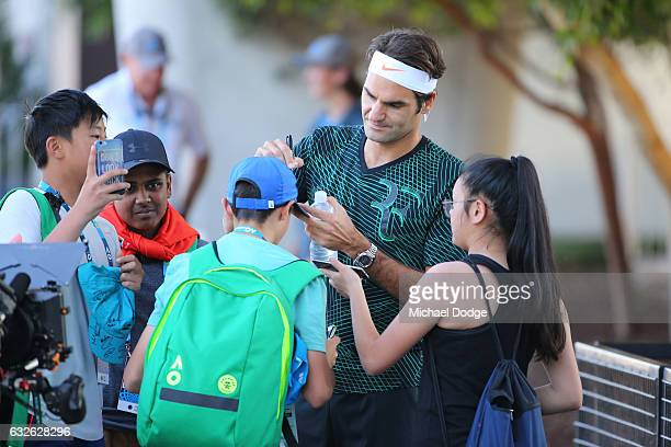 Roger Federer of Switzerland signs autographs for fans ahead of a practice session on day 10 of the 2017 Australian Open at Melbourne Park on January...