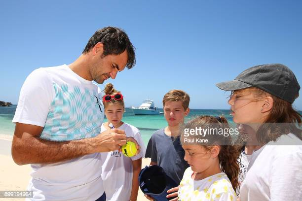 Roger Federer of Switzerland signs autographs on the beach for children at Rottnest Island ahead of the 2018 Hopman Cup on December 28 2017 in Perth...