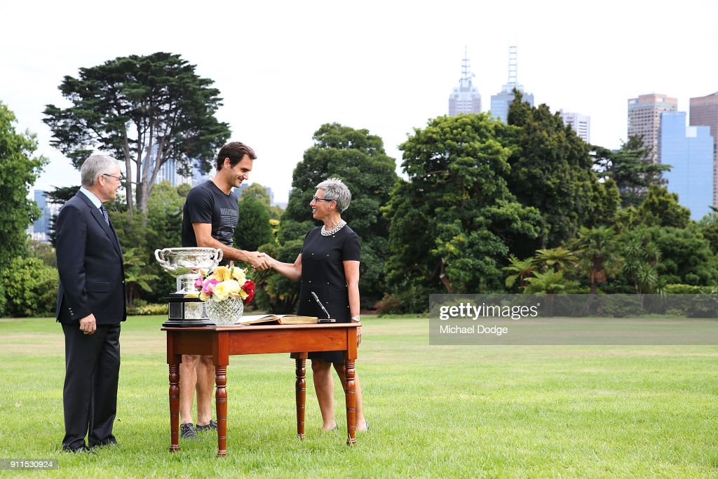 Roger Federer of Switzerland signs the visitors book with the Norman Brookes Challenge Cup alongside Governor Of Victoria, the Honourable Linda Dessau AM, and her husband Judge Anthony Howard after winning the 2018 Australian Open Men's Singles Final, at Government House on January 29, 2018 in Melbourne, Australia.