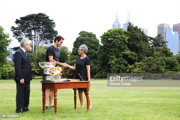 Roger Federer of Switzerland signs the visitors book with the Norman Brookes Challenge Cup alongside Governor Of Victoria the Honourable Linda Dessau...