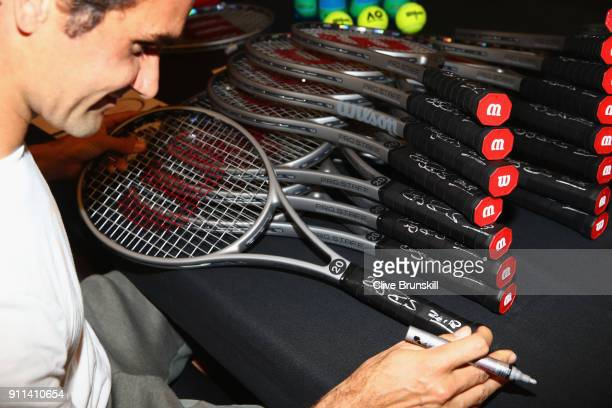 Roger Federer of Switzerland signs twenty Wilson Pro Staff commemorative tennis rackets to be sold for charity after winning his 20th grand slam...