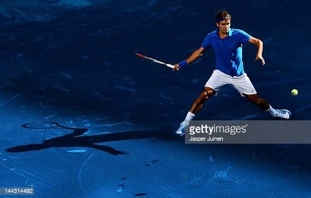 Roger Federer of Switzerland slides to play a backhand to Tomas Berdych of the Czech Republic in his final match during the Mutua Madrilena Madrid...